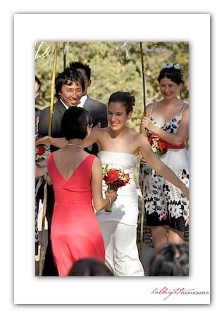 Bride hugs her friend while under the chuppah - Camp Arroyo Wedding