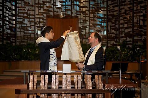 Bar Mitzvah and his father undress the torah at Temple Peninsula Sholom Burlingame