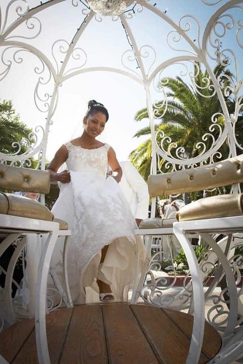 Bride wearing white entering her cinderella carriage   preservation park - oakland - wedding