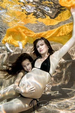 Underwater maternity portrait with mother, daughter and baby to be