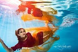 Underwater Portrait of female model in red dress - synchronized studio light shining into pool - ikelite - nikon